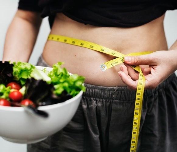 Mulher que tomou o Moder Diet Gold e se alimenta com produtos saudáveis mostra o resultado de emagrecimento.